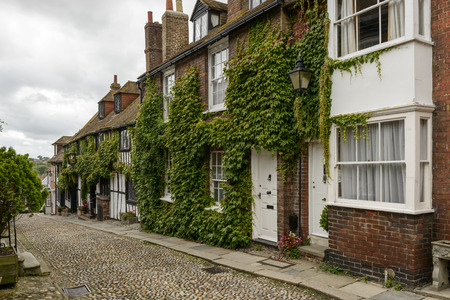 foreshortening of old cottages covered with vine on a downhill cobbled street in small  historic village of Rye, East Sussex Stock Photo