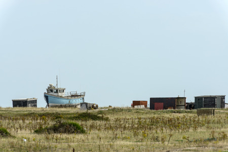 romney: view of  old fish boat aground and some sheds on the seaside at Dungedness,  Romney Marsh, Kent Stock Photo