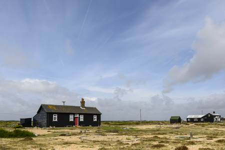 romney: landscape of the marsh with holiday bungalow painted in black near the seaside at Dungedness,  Romney Marsh, Kent