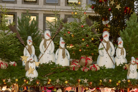 row of snowmen and decorated spruce  on stall roof in front of Town Hall at traditional Christmas market hold in city center, shot on dec 02 2014 , Stuttgart, Germany