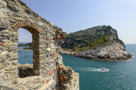 Palmaria island and stone window foreshortening of mediterranean island in La Spezia gulf with a stone window of St. Peter church in the foreground shot on a sunny spring day Portovenere Italy