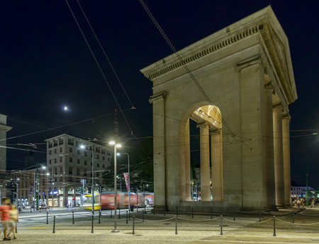 neoclassic: MILAN, ITALY - July 25: night life in the city center at EXPO time, side night view of Porta Ticinese monumental door under white moon with a passing trolley car, shot on jul 25 2015 Milan, Italy