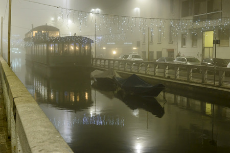 lightening: MILAN, ITALY - DECEMBER 8: night life in the city center at Xmas time, heavy fog floating pub on Xmas and lightening on Pavese Canal. Shot at night in foggy winter light on Dec. 8, 2015 Milan, Italy