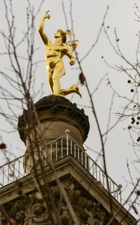gilt: gilt statue of Mercury on top of column in the historical city center of Stuttgart, shot in winter light Stock Photo