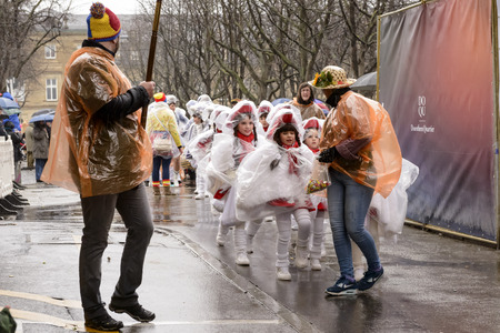wrapped up: STUTTGART, GERMANY - FEBRUARY 09: a group of majorettes in baby parade wrapped up in cellophane against h and light rain. Shot at Carnival parade in the city center on February 9, 2016 Stuttgart, Germany