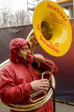 dressed up: STUTTGART, GERMANY - FEBRUARY 09: a tuba player plays while marching in a parade dressed up under light rain. Shot at Carnival parade in the city center on February 9, 2016 Stuttgart, Germany