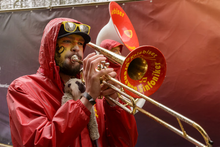 dressed up: STUTTGART, GERMANY - FEBRUARY 09: a trombone player plays while marching in a parade dressed up under light rain. Shot at Carnival parade in the city center on February 9, 2016 Stuttgart, Germany