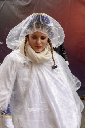 wrapped up: STUTTGART, GERMANY - FEBRUARY 09: wrapped up in cellophane against h and light rain, a nice girl dressed in white walks in the parade. Shot at Carnival parade in the city center on February 9, 2016 Stuttgart, Germany Editorial