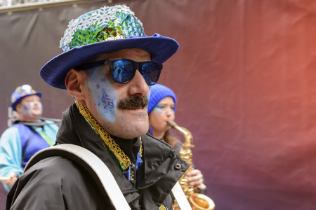 STUTTGART, GERMANY - FEBRUARY 09: a dressed up musician with mustache plays in the parade. Shot at Carnival parade in the city center on February 9, 2016 Stuttgart, Germany