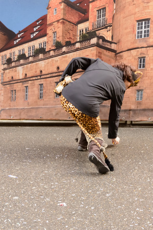 dressed up: STUTTGART, GERMANY - FEBRUARY 09: a woman dressed up picks up candy from the ground. Shot at Carnival parade in the city center on February 9, 2016 Stuttgart, Germany