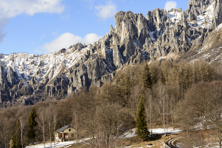 the crags: western cliffs of rocky peak in Lecco Grigna mountains in a winter with little snow, shot in bright winter light at Resinelli upland, Italy