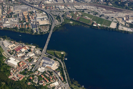 aerial shot, from a small plane, of bridge crossing the river Adda in Lecco town on shore of lake Como, Lombardy, Italy