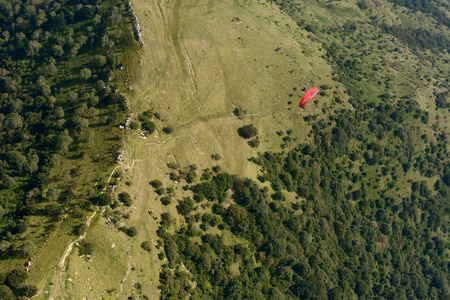 aerial shot, from a small plane, of red paraglider gliding above glades on Cornizzolo mountain, Lombardy, Italy