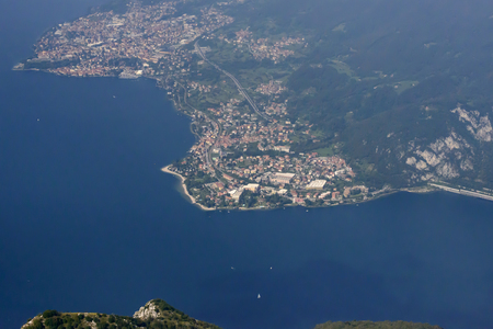 aerial shot, from a small plane, of villages of Mandello and Abbadia Lariana on shore of lake Como, Lombardy, Italy