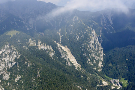 aerial shot, from a small plane, of a road made by a row of steep hairpin turns in the valley near Piazzatorre village, shot in the Orobie mountains, Bergamo, Lombardy, Italy