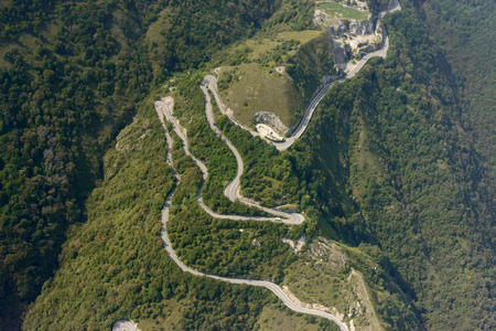 aerial shot, from a small plane, of a mountain road with hairpin turns That leads to Selvino village, shot in the Orobie mountains, Bergamo, Lombardy, Italy Stock Photo