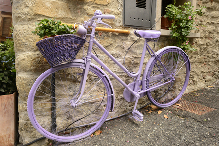 old bike totally painted lilac parked near stone wall at Lerma, Italy Stock Photo