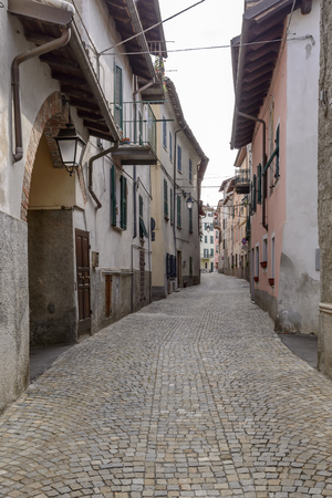 view of old houses and narrow street in bending small village of Rocca Grimalda Piedmont, Italy
