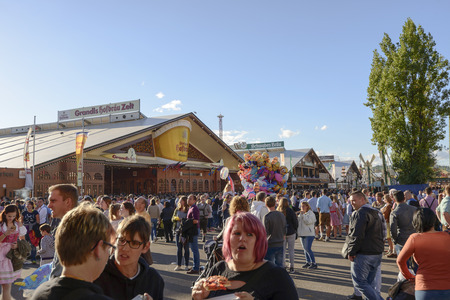STUTTGART, GERMANY - OCTOBER 02: view of crowd of visitors among large traditional food stalls in the carnival. Shot at Oktoberfest in city center on oct 02, 2016 Stuttgart, Germany