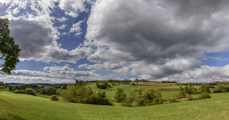 hilly landscape with green fields under bright thick clouds in the German countryside. Shot in bright light near Bonndorf, Baden Wuttenberg, Germany Stock Photo