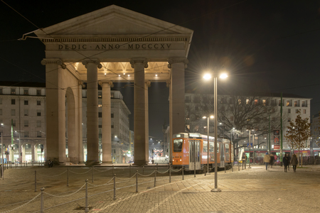 MILAN, ITALY - DECEMBER 22: a trolley car passes by monumental Porta Ticines at Christmas time on a quiet weekday evening, shot on dec 22 2016 Milan, Lombardy, Italy