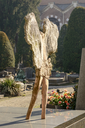rear view of angel stone sculpture at big monumental Cemetery in town, shot in bright winter light late in Milan, Lombardy, Italy