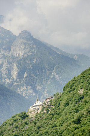 Mountainous little village and abbey on a steep slope, shot on a bright summer day at Notre Dame de la Garde, Lys valley, Aosta, Italy Stock Photo