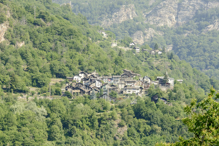 Mountain small village on a steep slope, shot on a bright summer day at Chamioux, Lys valley, Aosta, Italy
