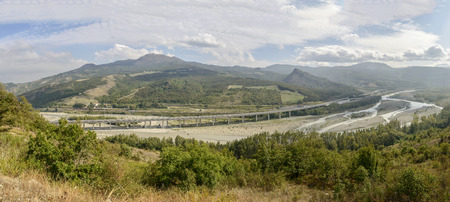 landscape of the Pennine Taro river valley with long Cisa highway viaduct crossing the river and railway near, shot in bright late summer light near Oriano, Parma, Italy Stock Photo