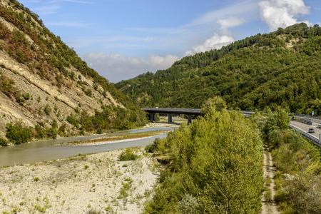 landscape with Cisa highway bridge over the Pennine Taro river, shot in bright late summer light near Solignano, Parma, Italy Stock Photo