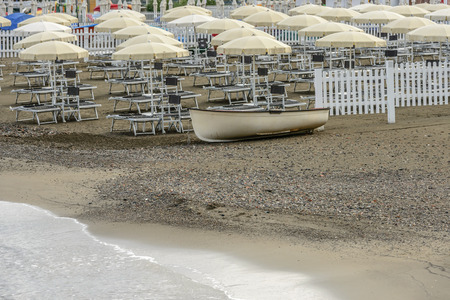 landed boat and deck chairs at the beach in Sestri Levante, Genoa, Liguria, Italy