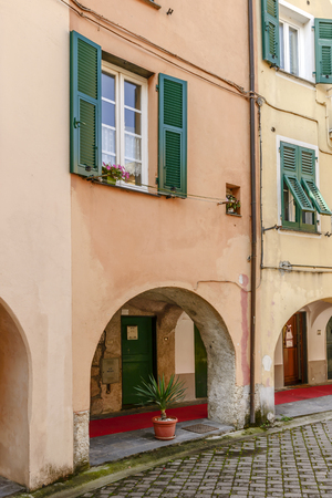 Foreshortening of picturesque arches of covered walkway under old medieval houses, shot in bright late summer light at Varese Ligure, Genoa, Liguria, Italy