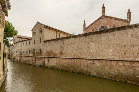 View of exterior brick wall of san francisco monastery on canal Rio flowing in city center, shot in bright cloudy light at Mantua, Lombardy, Italy Stock Photo
