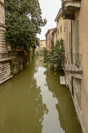 View of lush vegetation and old houses on canal Rio flowing in city center, shot in bright cloudy light at Mantua, Lombardy, Italy