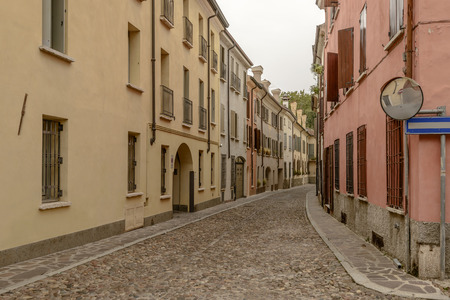 view of old houses on bending cobbled street in city center, shot in bright cloudy light at Mantua, Lombardy, Italy