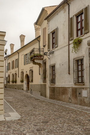 view of old houses on cobbled street in city center, shot in bright cloudy light at Mantua, Lombardy, Italy Editorial