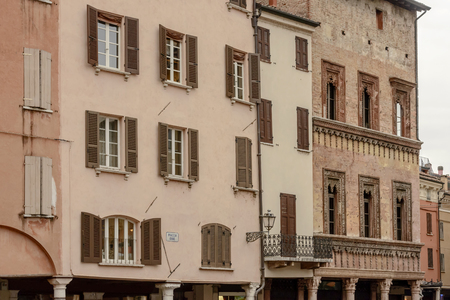 detail of facades of historic buildings on Erbe square, shot in bright cloudy light at Mantua, Lombardy, Italy