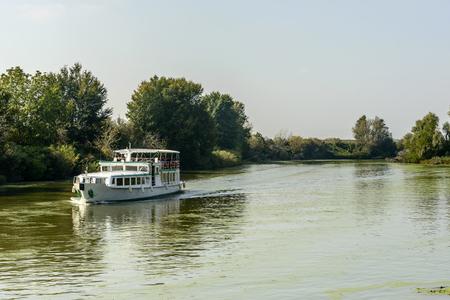 view of tourist cruise ship on Mincio river, shot in bright autumn sunlight near Mantua, Lombardy, Italy Editorial
