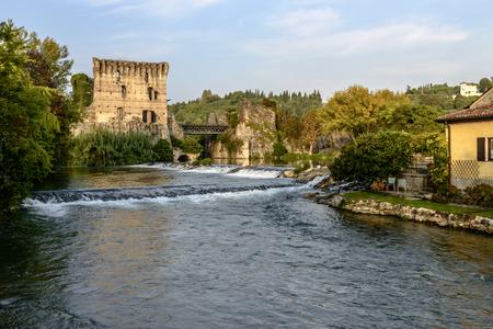 view of small waterfalls and old bridge over Mincio river, shot in bright fall light at Valeggio, Verona, Veneto, Italy