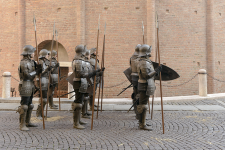 MANTUA, ITALY - OCTOBER 1: extras dressed as a picket of Renaissance soldiers walking along San Francesco church during the shooting of a costume drama; shot on Oct 1 2017 in Mantua, Italy Редакционное