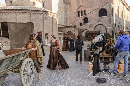 MANTUA, ITALY - OCTOBER 1: extras dressed as Renaissance courtiers and tramps near San Francesco church during the shooting of a costume drama; shot on Oct 1 2017 in Mantua, Italy Фото со стока - 90125245