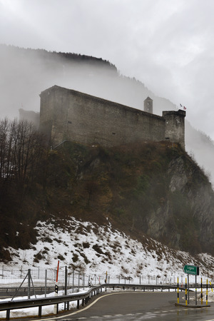 medieval castle looming among low clouds in valley winter landscape, shot in bright cloudy light at Mesocco, Ticino, Switzerland Stock Photo