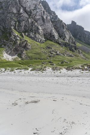 landscape with bright white sand beach and steep rock crags at bay on western side of island, shot under bright summer light at Bleik, Andoya, Vesteralen, Norway