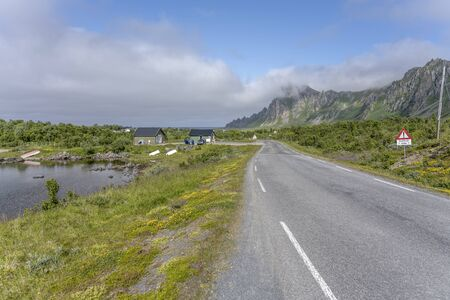 landscape with road in green countryside near lake and hills just out of Artic village on western side of island, shot under bright summer light at Bleik, Andoya, Vesteralen, Norway