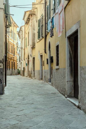 cityscape with old buildings on narrow bending street in town historical center, shot at Carrara, Tuscany, Italy Banco de Imagens