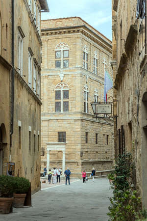 PIENZA, ITALY - september 23 2020: cityscape with people strolling in front of Renaissance Piccolomini palace on central street of historical town, shot in bright light on september 23 2020 at Pienza, Siena, Tuscany, Italy