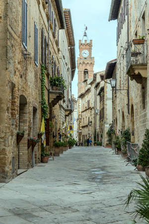 PIENZA, ITALY - september 23 2020: cityscape with town hall tower looming at central street of historical town, shot in bright light on september 23 2020 at Pienza, Siena, Tuscany, Italy Editorial