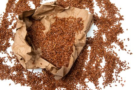 isolated pile of flaxseed scattered on a white background and craft paper