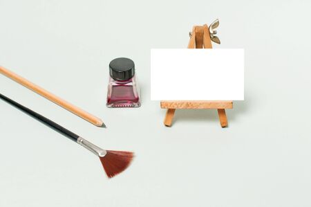 an easel with an empty sheet of paper for your text, maroon ink, a wide brush and a black pencil