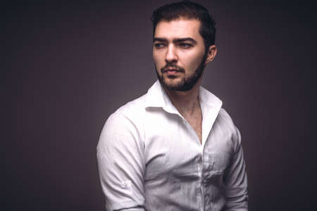 Portrait of handsome man of caucasian appearance with beard in white shirt. Serious confident guy looks away. Studio